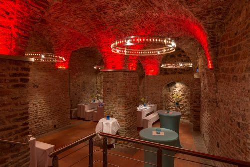 Gewölbekeller der Klarissenklosters mit roter LED-Beleuchtung, runde Stehtische, Bierzeltgarnituren mit weißen Hussen, Backsteinmauern