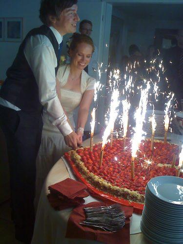 Brautpaar schneidet zusammen Kuchen an, großer Erdbeerkuchen, angerichtet mit Feuerwerk