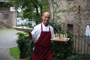 Axel Schellhas, lächelt in die Kamera, Koch trägt zwei Platten, Salat, Fingerfood