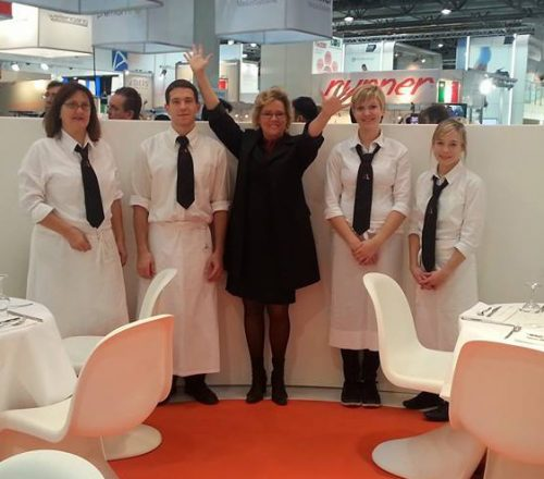 Frauke Schellhas steht zwischen vier Mitarbeitern, Alle lächeln in die Kamera, Mitarbeiter tragen weiße Hemden, Blusen und Schürzen, schwarze Krawatte mit Logo der Firma Schellhas Event & Catering