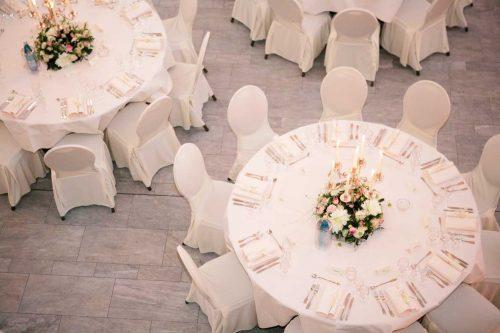 Gedeckte runde Tisch von oben, beige Decken und Stuhlhussen, Blumendekoration in der Mitte, Steinboden