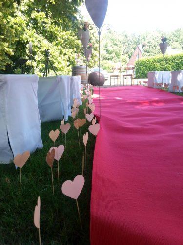Dekoration mit vielen kleinen Herzen, die neben einem roten Teppich in den Boden gesteckt sind. Roter Teppich führt zwischen Bänken zu den Plätzen des Brautpaars, freie Trauung